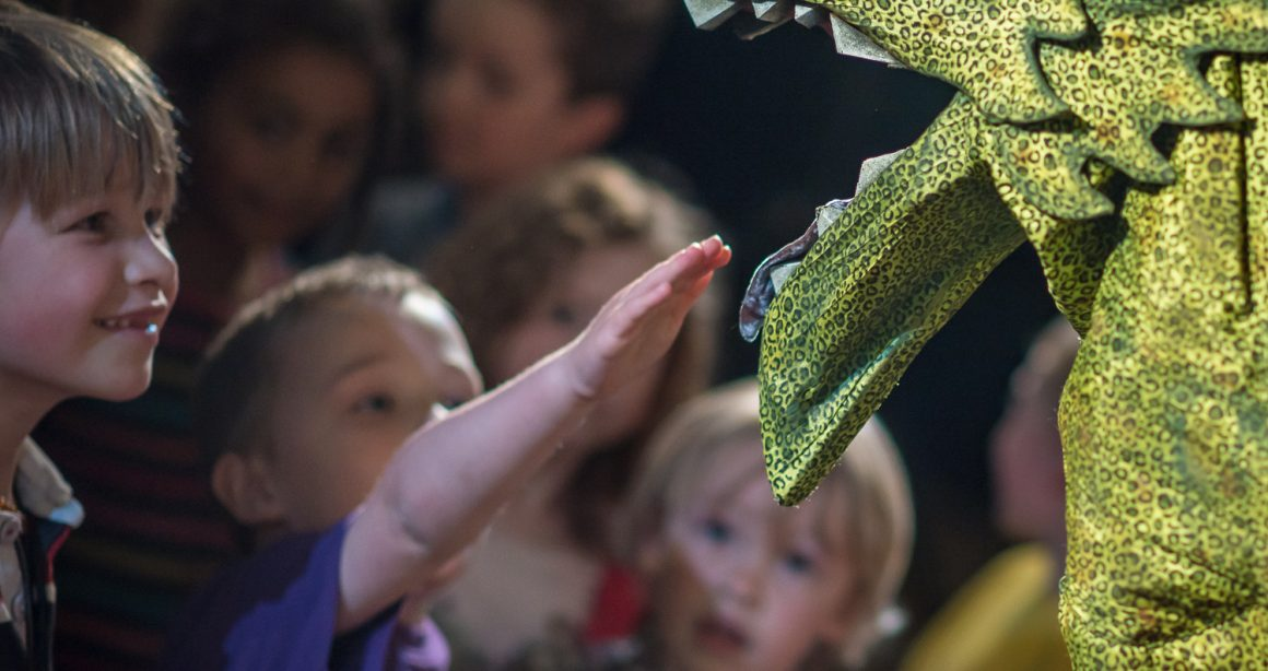 Dragon Puppet, child putting his hand in the dragon's mouth during Puppet Animation Festival