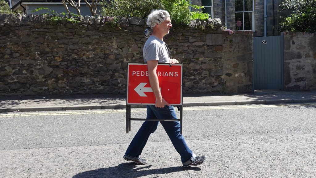 Visual for Extremely Pedestrian Chorales, a man with a white powdered wig, walks cross an empty street, facing to the right, holding a red Pedestrian sign, an arrow pointing to the left.