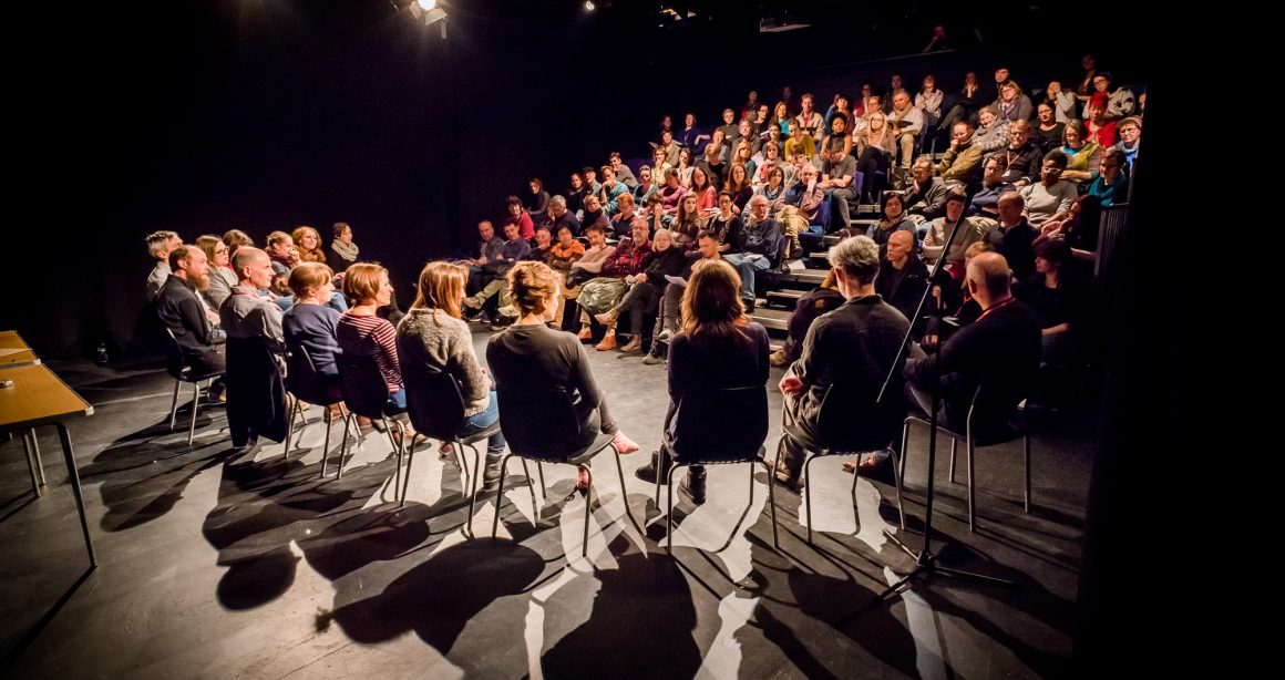 A group of around ten people sit on chairs in a semi circle on a small stage, their back to the camera, in front of an audience in a small theatre room. The light is directed at the stage.