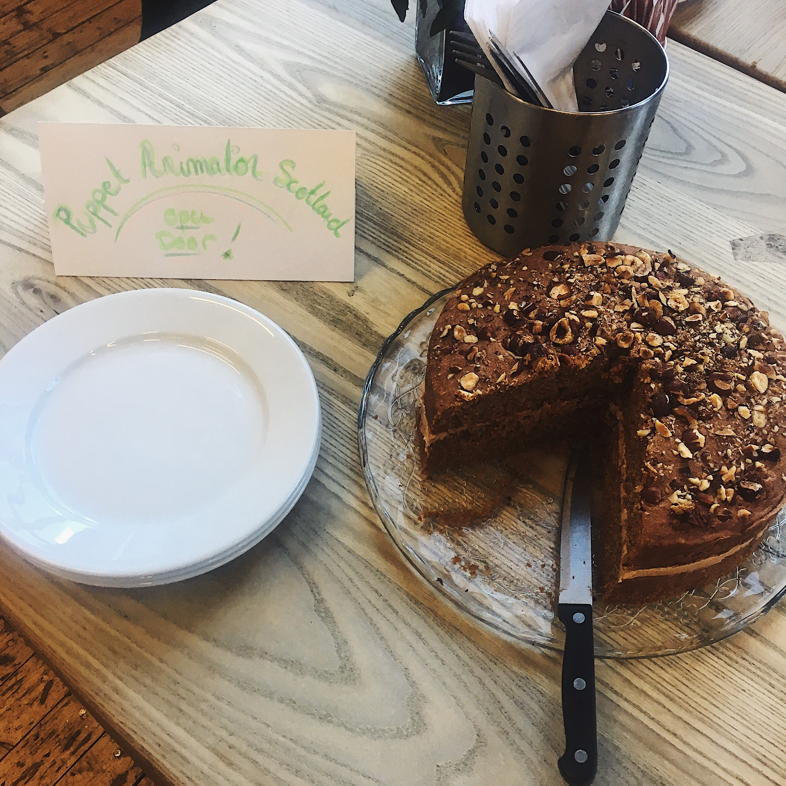 """a two layers brown hazelnut cake sits on a plate, a slice cut out of it and the knife still in place, to the right hand side of the photo. On the left, a pile of empty plates and a sign reading """"Puppet Animation Scotland Open Doors"""". The whole is on a wooden table."""